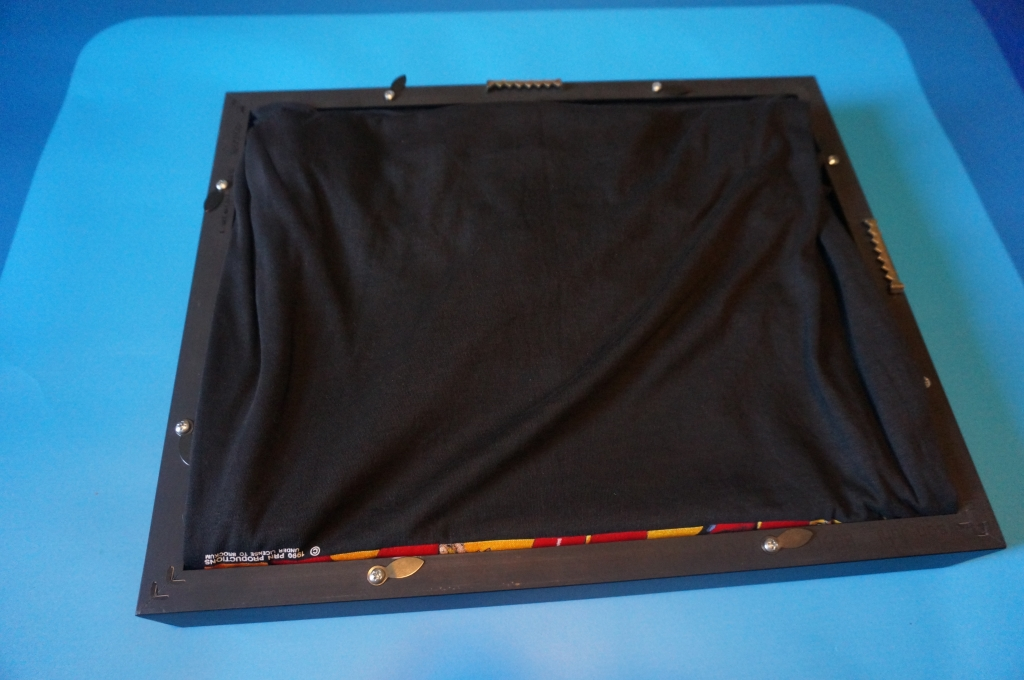 neatly organize the remaining fabric of the shirt inside the frame